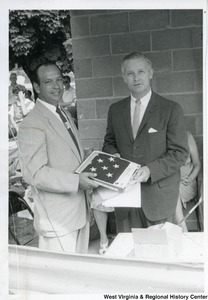 Congressman Arch A. Moore, Jr. and an unidentified man holding an American Flag during the Ida May dedication.