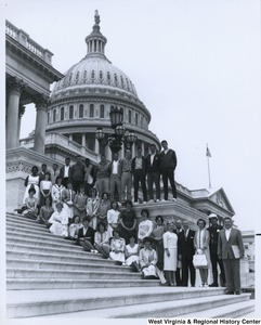 Congressman Arch A. Moore, Jr. standing at the bottom of the Capitol steps with an unidentified group of men and women.
