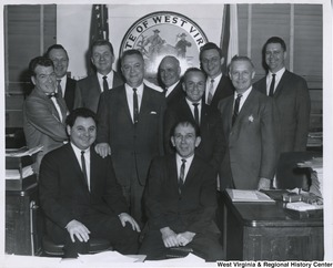 Congressman Arch A. Moore, Jr. with a group of men presumed to be working on the Harmon Creek Watershed. Front Row, Left to Right:   Paul Altomarice, John Fozzi; 2nd Row, Left to Right: John C. Moore, Mayor Frank Rybka, Chester Barnabie, Congressman Arch A. Moore; Back Row, Left to Right: Edie Mallnowski, Pete Sokalowski, Thos Evans, James Lord, City Manager and John Cromwell.