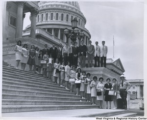 An unidentified group of men and women standing on the steps of the Capitol.