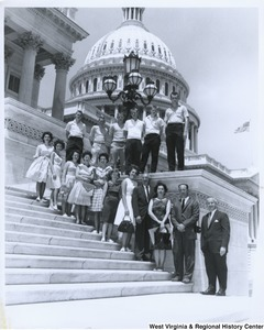 Congressman Arch A. Moore, Jr., at the bottom of the steps, with an unidentified group of men and women on the steps of the Capitol.