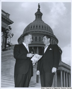 Congressman Arch A. Moore, Jr. standing with an unidentified man on the Capitol steps. Moore is pointing to something on a paper he is holding, which appears to contain information about the Capitol.