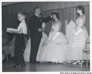 Congressman Arch A. Moore, Jr. placing a tiara on the head of an unidentified woman in a formal dress. Two other women in formal wear are standing on either side of her.
