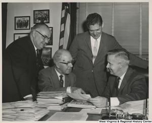 Congressman Arch A. Moore, Jr. (seated on the right) in a discussion with three unidentified men.