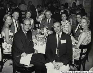 Congressman Arch A. Moore, Jr. and his wife, Shelley, seated with an unidentified group of men and women at a party.