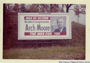 "A billboard that states ""Re-elect Congressman Arch Moore; Man of Action; The Man for you."""