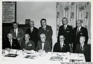 Congressman Arch A. Moore, Jr. (seated, first on the left) with nine unidentified men. Four of them are sitting with Moore, while the other five are standing behind them.