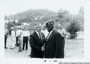 Congressman Arch A. Moore, Jr. shaking the hand the of unidentified Fairmont (W.Va.) veteran. People can be seen standing around in the background.