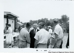 Congressman Arch A. Moore, Jr. shaking the hand of a veteran, possibly in Fairmont, W.Va. Two other men are beside him, and they all appear to be having a discussion.
