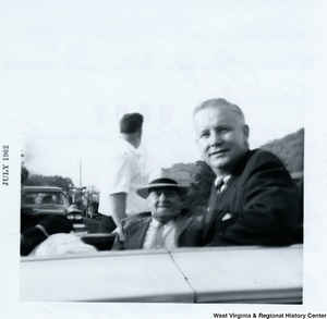 Congressman Arch A. Moore, Jr. sitting in what appears to be the back of a vehicle with Harry Fryer.