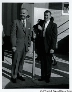 Congressman Arch A. Moore, Jr. standing with an unidentified man who is leaning against a parking meter.