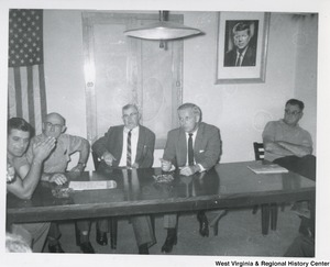 Congressman Arch A. Moore, Jr. having a discussion with four unidentified men. They are all seated at a table. There is an American flag and a framed photograph of President John F. Kennedy in the background.