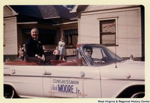 Congressman Arch A. Moore, Jr. sitting in the back of a vehicle. The side of the vehicle has a Congressman Arch Moore, Jr. sign taped to it.