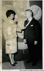 Congressman Arch A. Moore, Jr. receiving  a medal from an unidentified woman. She is holding the end of the medal in her hands, and they appear to be having a conversation.
