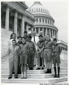 Congressman Arch A. Moore, Jr. standing on the steps of the Capitol with a small group of Boy Scouts.