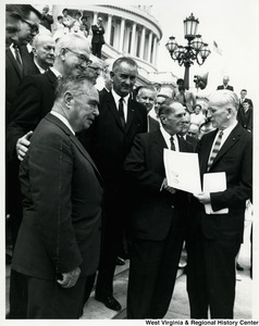 General of the Army Douglas MacArthur receives from the House Speaker John McCormack a certificate of appreciation authorized by Congress. At left is Vice President Lyndon Johnson. Congressman Arch Moore is in the background.