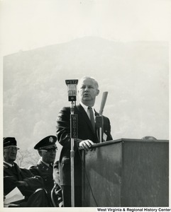 "Congressman Arch A. Moore, Jr. speaking outdoors at a podium. A microphone labeled with the letters ""WETZ""is in the foreground."