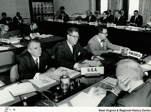 A group of officials from the United States and Venezuela taking notes during a meeting.
