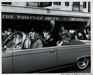Congressman Arch A. Moore, Jr and his son, Kim, sitting in the back of a car during a parade.