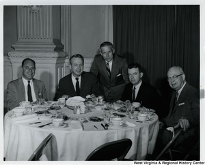 Congressman Arch A. Moore, Jr. standing behind a table where four unidentified men are sitting.