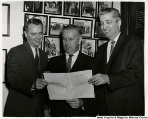 Congressman Arch A. Moore, Jr. with two unidentified people looking at the bill, H.R. 7457, the Criminal Justice Act of 1964 (S. 1057).