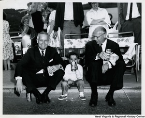 Congressman Arch A. Moore, Jr. sitting on a curb and drinking a soda with an unidentified little boy and man.