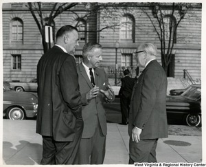 Congressman Arch A. Moore, Jr. (center) talking to two unidentified men outside.