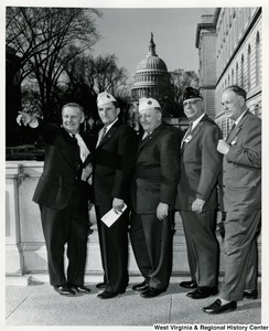 Congressman Arch A. Moore, Jr. pointing out something to four unidentified Veterans of Foreign Wars.