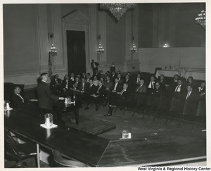 Congressman Arch A. Moore, Jr. speaking to a group of men and women in what appears to be a hearing room.