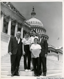 Congressman Arch A. Moore, Jr. standing on the steps of the Capitol Building with a family of four.