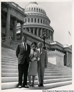 Congressman Arch A. Moore, Jr. standing on the steps of the Capitol Building with an unidentified man and woman.