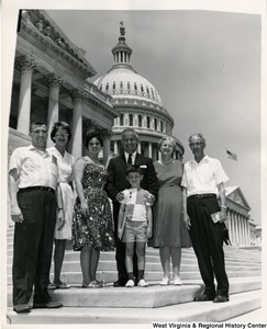 Congressman Arch A. Moore, Jr. standing with an unidentified family of six on the steps of the Capitol Building.