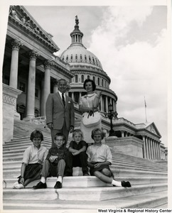 Congressman Arch A. Moore, Jr. standing with an unidentified woman on the steps of the Capitol. Seated in front of them are four children.