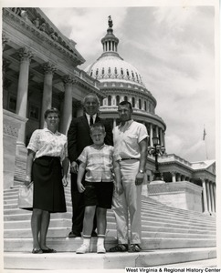 Congressman Arch A. Moore, Jr.  standing with an unidentified family of three on the steps of the Capitol Building.