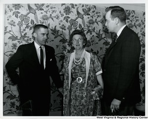 Two unidentified men and one women having a conversation.