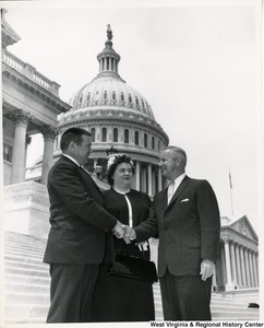 Congressman Arch A. Moore, Jr. shaking hands with an unidentified man on the steps of the Capitol Building. An unidentified woman is standing beside them.