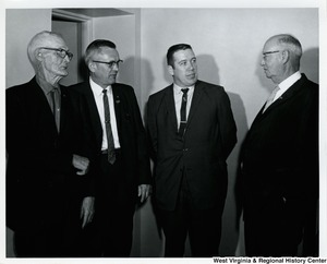 Four unidentified men in conversation.