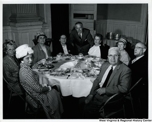 Congressman Arch Moore, Jr. standing behind a table of unidentified men and women.