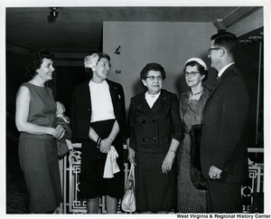 Four unidentified women and one man having a conversation.