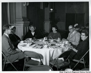 A table of unidentified men and women in conversation.
