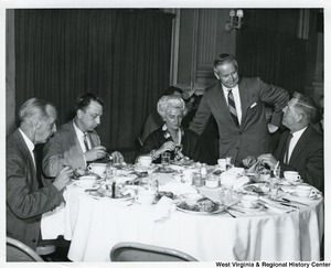Congressman Arch A. Moore, Jr. leaning against a chair, which a woman is seated in, talking to an unidentified man. There are two other unidentified men at the table.