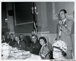 Congressman Arch A. Moore, Jr. seated fifth from the left, listening to an unidentified man give a speech.