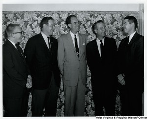 Five unidentified men having a conversation.