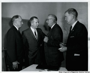 Four unidentified men having a conversation.