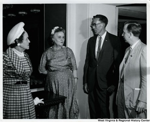 Two unidentified men and two unidentified women having a conversation.
