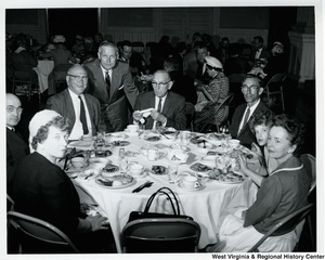 Congressman Arch A. Moore, Jr.  leaning against two chairs at a table of unidentified men and women.