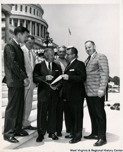 Congressman Arch A. Moore, Jr. showing a book to a group of unidentified men. They are standing on the steps of the Capitol Building.