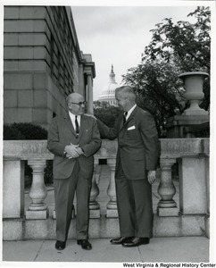 Congressman Arch A. Moore, Jr. standing with his hand on an unidentified man's shoulder. The Capitol Building can be seen in the background.