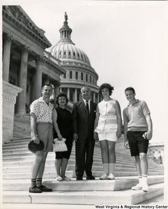 Congressman Arch A. Moore, Jr. standing with an unidentified family of four on the steps of the Capitol.