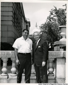 Congressman Arch A. Moore, Jr. with an unidentified man. The Capitol Building can be seen in the background.